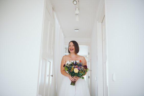 Bruid staat te wachten met boeket voordat ze haar aanstaande voor het eerst ziet first look tijdens bruiloft in fruittuin trouwfotograaf Amsterdam Apeldoorn
