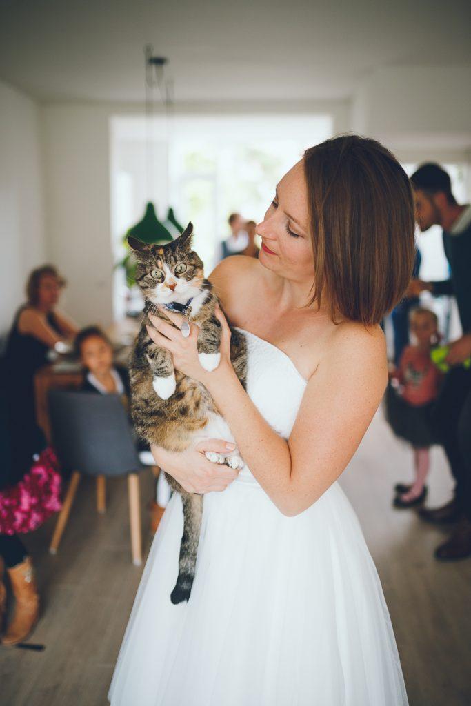 Bruid knuffelt met kat tijdens bruiloft in fruittuin trouwfotograaf Amsterdam Apeldoorn