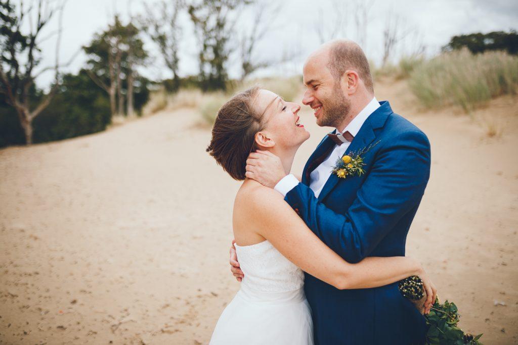 Bruidspaar kijkt elkaar lief aan tijdens fotoshoot in de duinen bij Zuid Kennemerland Bloemendaal tijdens bruiloft in fruittuin trouwfotograaf Amsterdam Apeldoorn