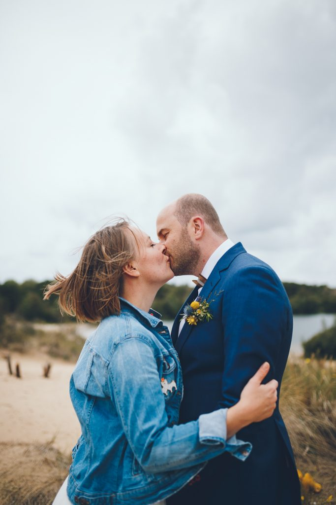 Bruidspaar kust elkaar tijdens fotoshoot in de duinen bij Zuid Kennemerland Bloemendaal tijdens bruiloft in fruittuin trouwfotograaf Amsterdam Apeldoorn