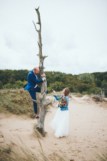 Bruidegom klimt in boom tijdens fotoshoot in de duinen bij Zuid Kennemerland Bloemendaal tijdens bruiloft in fruittuin trouwfotograaf Amsterdam Apeldoorn