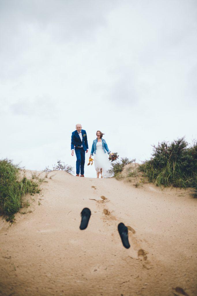 Bruidspaar gooit slippers naar beneden tijdens fotoshoot in de duinen bij Zuid Kennemerland Bloemendaal tijdens bruiloft in fruittuin trouwfotograaf Amsterdam Apeldoorn
