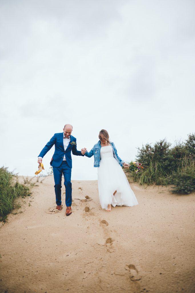 Bruidspaar loopt hand in hand naar beneden tijdens fotoshoot in de duinen bij Zuid Kennemerland Bloemendaal tijdens bruiloft in fruittuin trouwfotograaf Amsterdam Apeldoorn