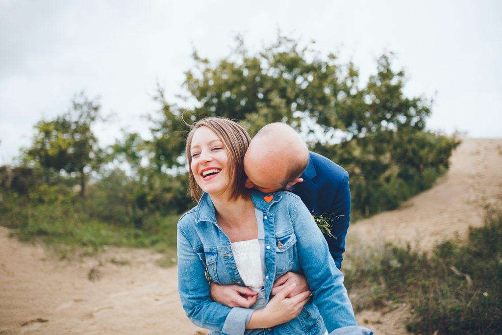 Bruidegom omhelst bruid tijdens fotoshoot in de duinen bij Zuid Kennemerland Bloemendaal tijdens bruiloft in fruittuin trouwfotograaf Amsterdam Apeldoorn