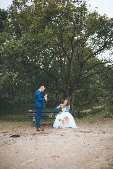 Bruidspaar zit op bankje steentjes uit hun schoenen te plukken tijdens fotoshoot in de duinen bij Zuid Kennemerland Bloemendaal tijdens bruiloft in fruittuin trouwfotograaf Amsterdam Apeldoorn