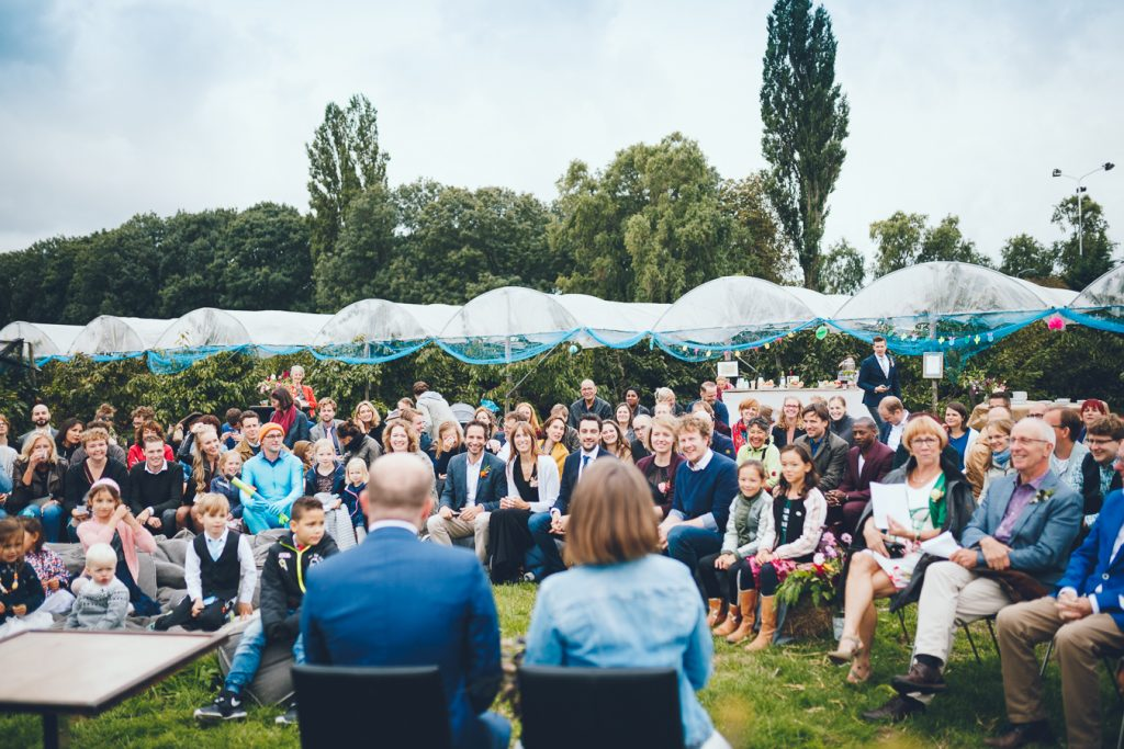 Trouwceremonie gasten op hooibalen tijdens bruiloft in fruittuin trouwfotograaf Amsterdam Apeldoorn