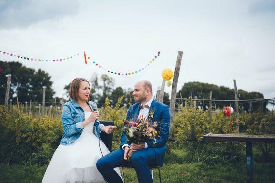 Bruidspaar spreekt elkaar aan tijdens ceremonie tijdens bruiloft in fruittuin trouwfotograaf Amsterdam Apeldoorn