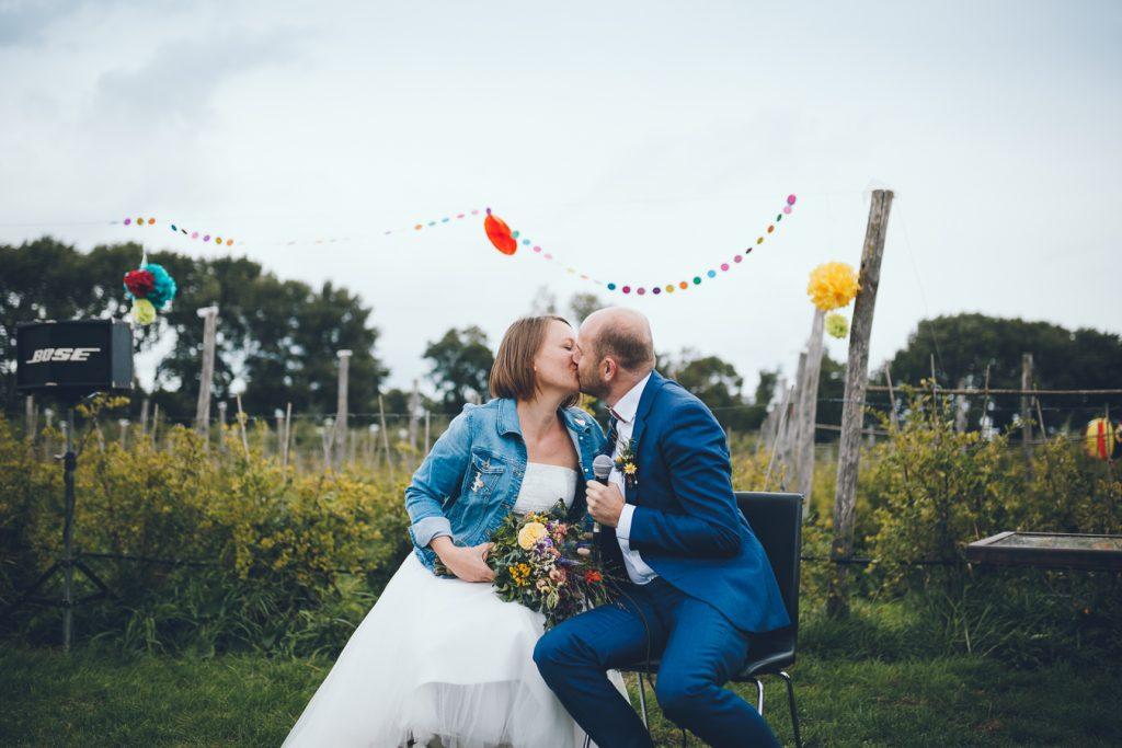 Bruidspaar kust elkaar tijdens bruiloft in fruittuin trouwfotograaf Amsterdam Apeldoorn