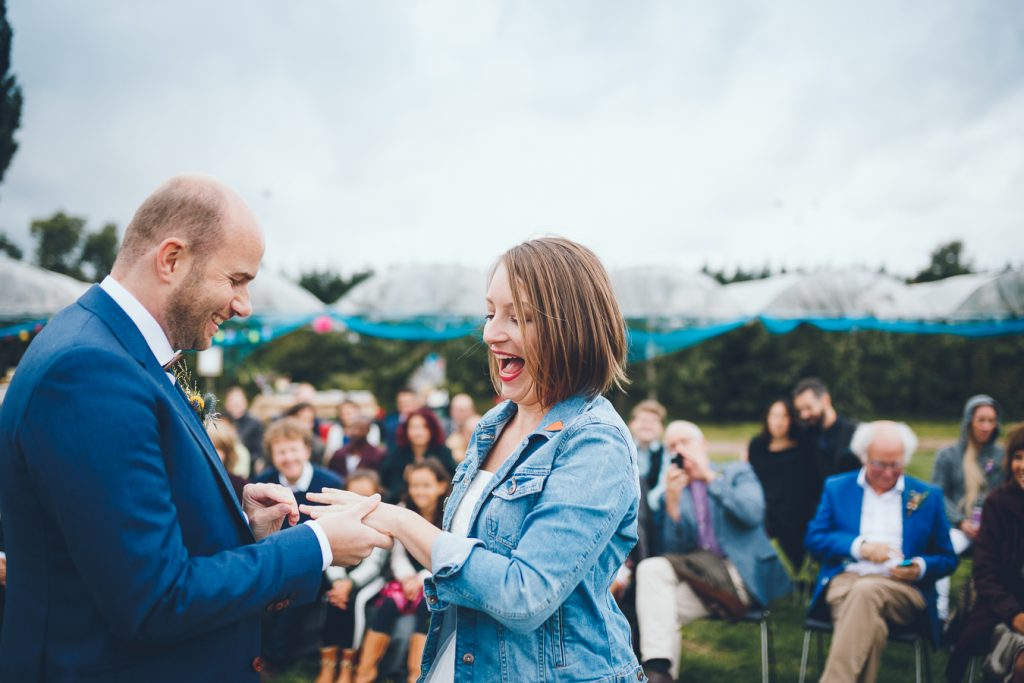Bruid krijgt ring om vinger tijdens bruiloft in fruittuin trouwfotograaf Amsterdam Apeldoorn