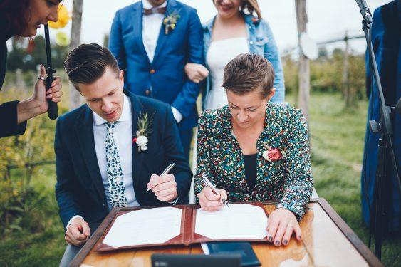 Getuigen tekenen tijdens bruiloft in fruittuin trouwfotograaf Amsterdam Apeldoorn