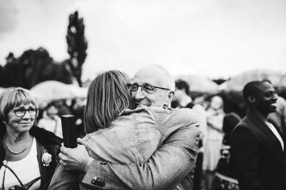 Vader omhelst dochter de bruid zwart wit tijdens bruiloft in fruittuin trouwfotograaf Amsterdam Apeldoorn