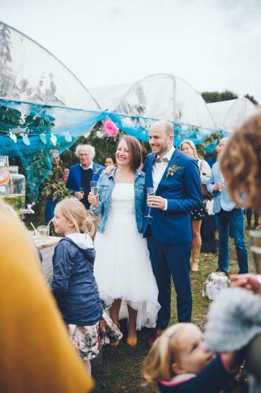 Bruidspaar luistert naar speech tijdens bruiloft in fruittuin trouwfotograaf Amsterdam Apeldoorn