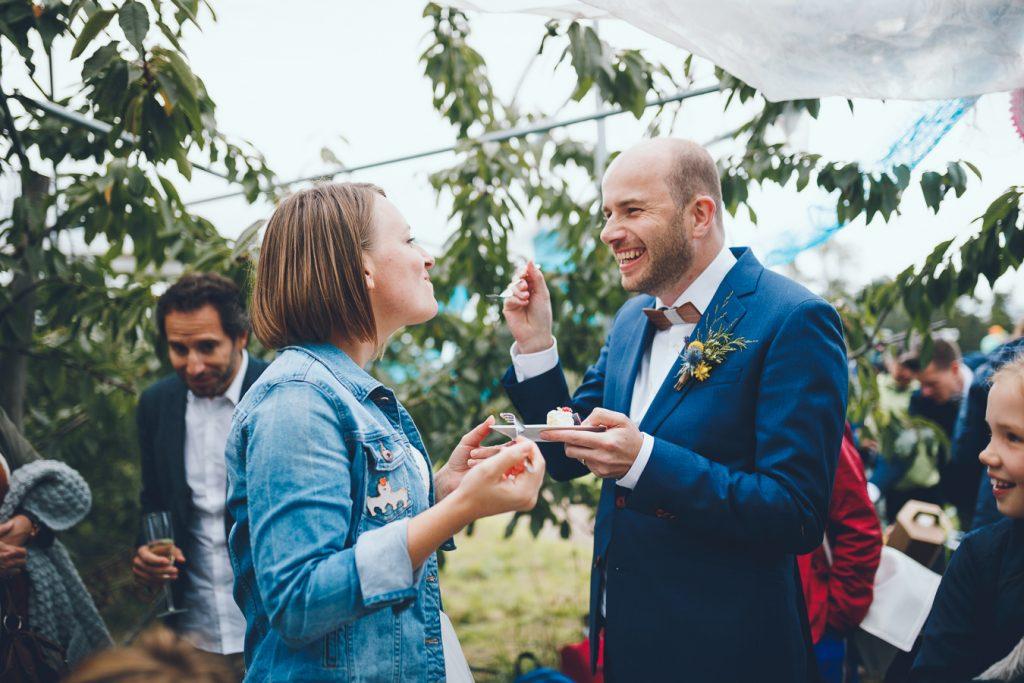 Bruidegom geeft bruid hapje van bruidstaart tijdens bruiloft in fruittuin trouwfotograaf Amsterdam Apeldoorn