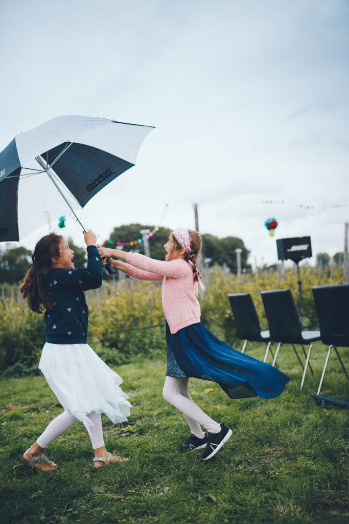 Twee meisjes dansen onder een paraplu tijdens bruiloft in fruittuin trouwfotograaf Amsterdam Apeldoorn