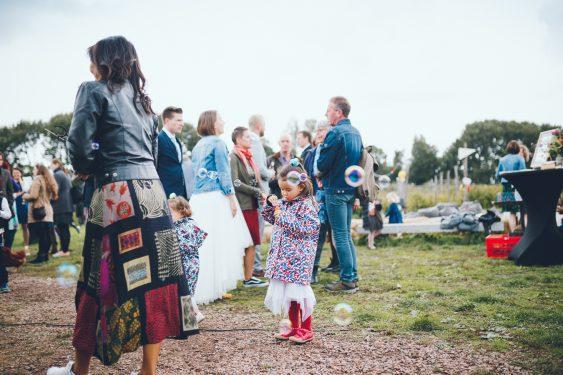 Meisje in rode laarzen blaast bellen tijdens bruiloft in fruittuin trouwfotograaf Amsterdam Apeldoorn