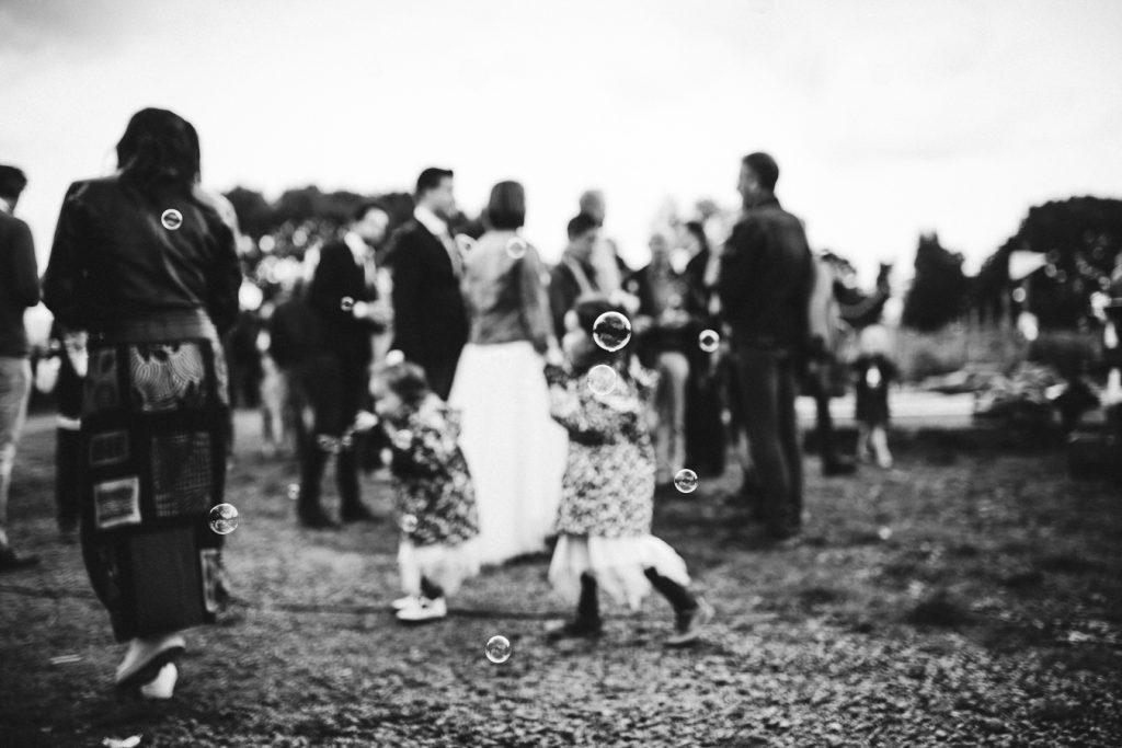Bellen blazen in zwart wit tijdens bruiloft in fruittuin trouwfotograaf Amsterdam Apeldoorn