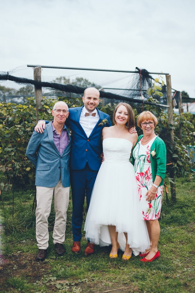 Groepsfoto familie van de bruid tijdens bruiloft in fruittuin trouwfotograaf Amsterdam Apeldoorn
