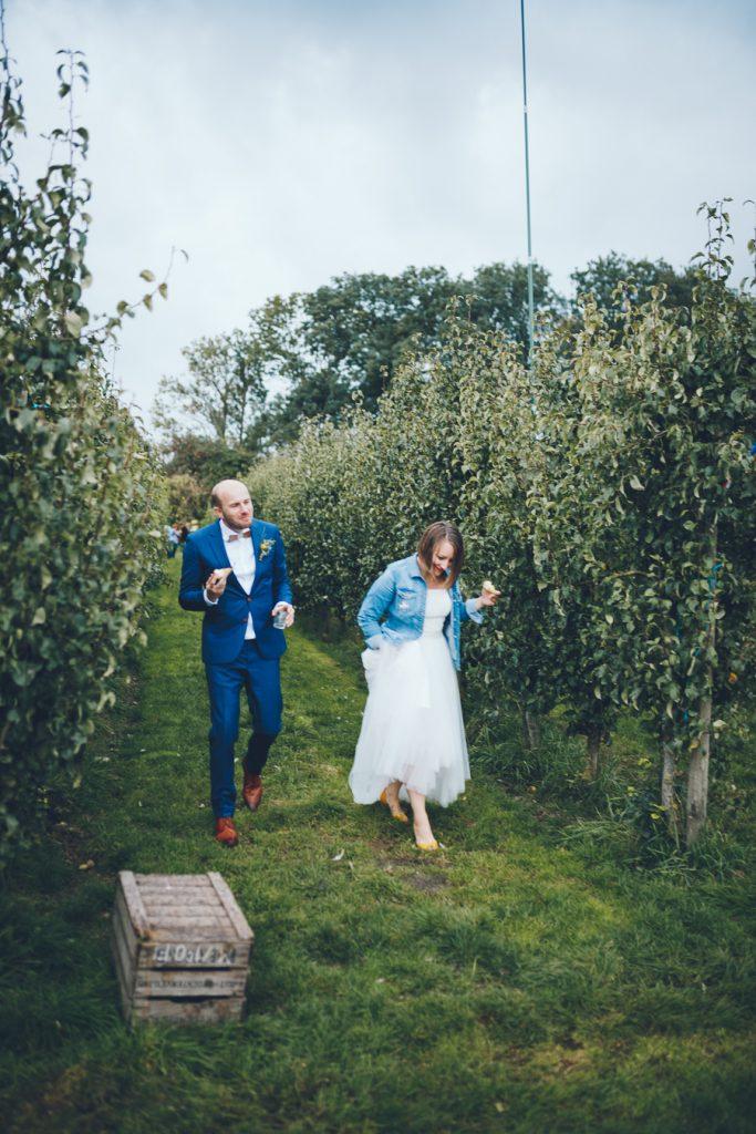 Bruidspaar plukt fruit tijdens bruiloft in fruittuin trouwfotograaf Amsterdam Apeldoorn