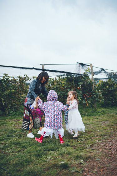 Meisjes en moeder dansen in een kring tijdens bruiloft in fruittuin trouwfotograaf Amsterdam Apeldoorn