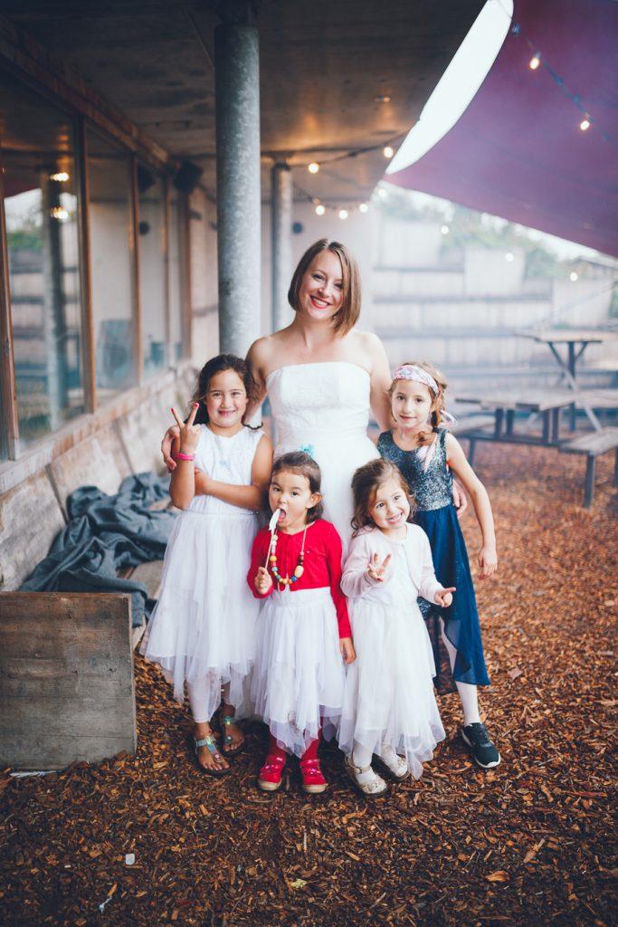 Bruid op de foto met meisjes tijdens bruiloft in fruittuin trouwfotograaf Amsterdam Apeldoorn