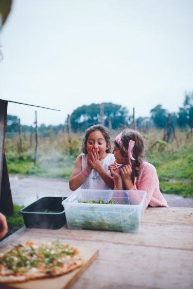 Twee meisjes kijken verlekkerd en blij naar pizza's die gebakken worden tijdens bruiloft in fruittuin trouwfotograaf Amsterdam Apeldoorn