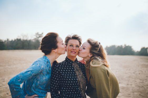 Familiefotograaf Kootwijkerzand Apeldoorn moeder met twee dochters die kus geven op wang