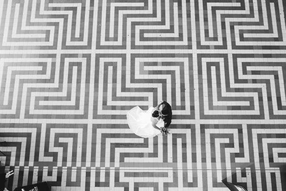 Bruid en bruidegom dansen op de zwartwitte vloer bij Radio Kootwijk in het Radiogebouw dichtbij Apeldoorn