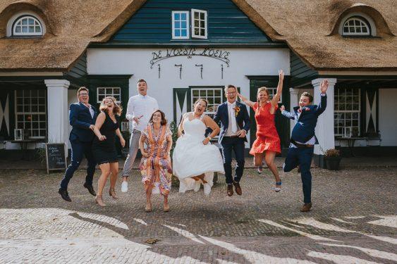 Groep vrienden en vriendinnen springen met bruid en bruidegom bij de Woeste Hoeve