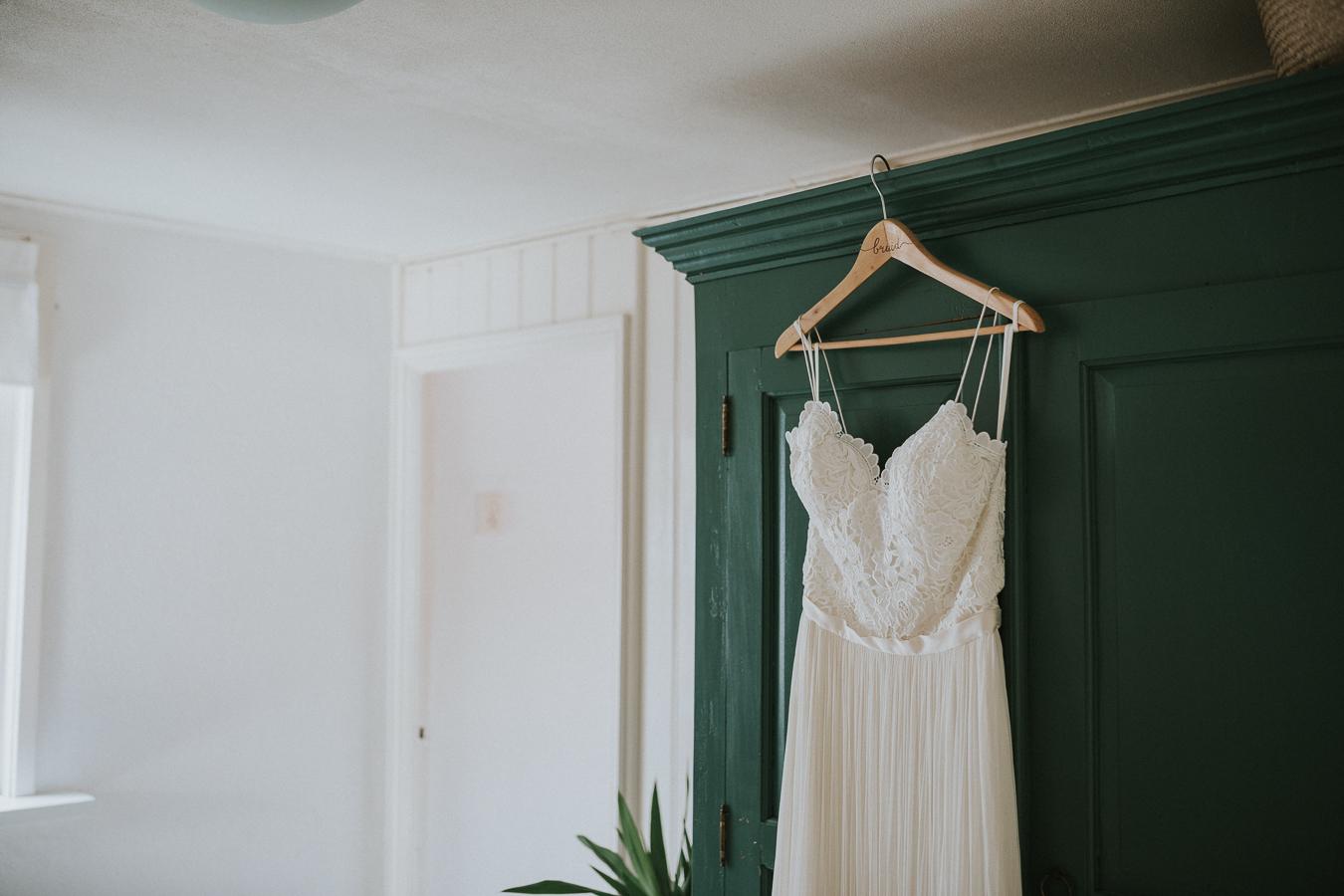 Trouwjurk hangt op gegraveerde hanger aan groene kast ter voorbereiding bruid