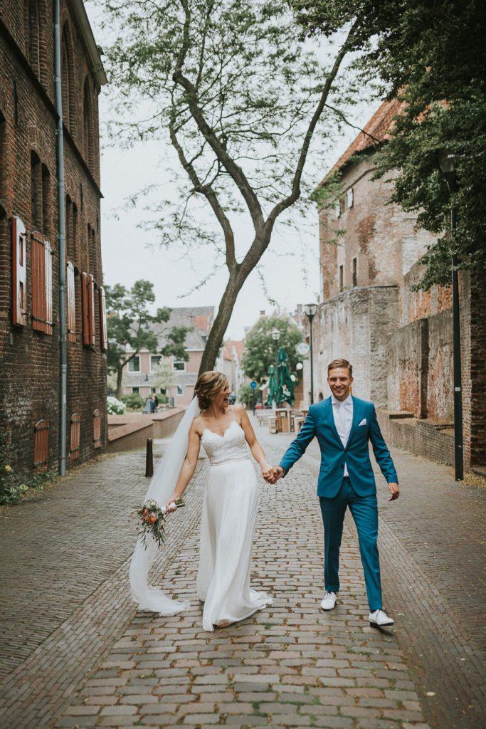 Boho bruidspaar loopt hand in hand in oude stadscentrum van Zwolle