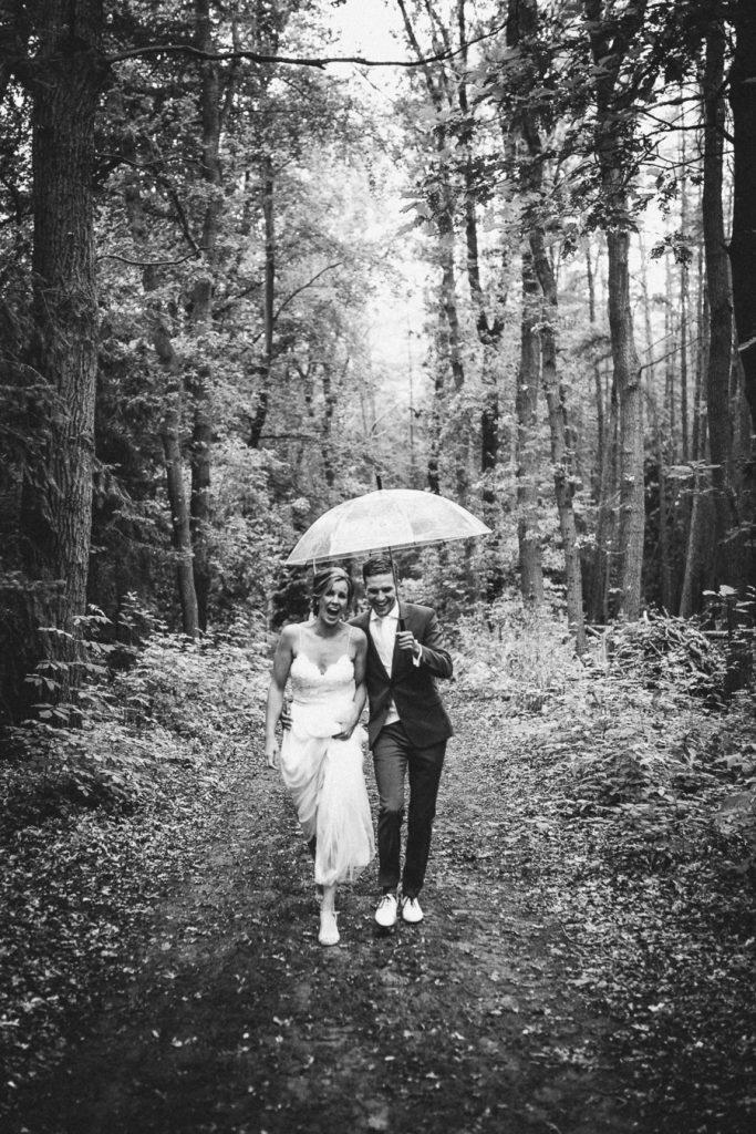 Bruidspaar loopt in bos in de regen onder transparante paraplu en lacht