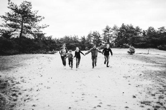 Familie rent hand in hand en lachend op Kootwijkerzand
