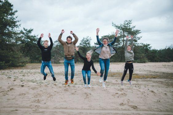 Familie springt met de handen in de lucht tijdens familiefotosessie