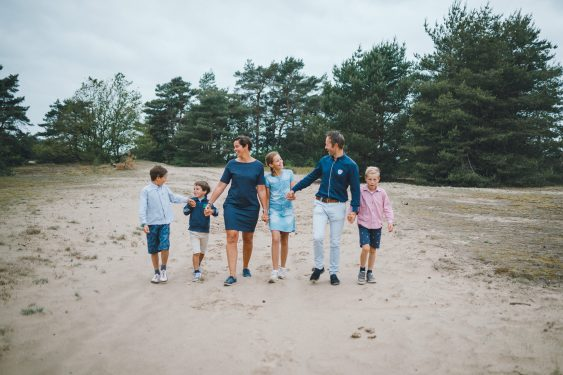 Familie loopt hand in hand en lachend op Kootwijkerzand