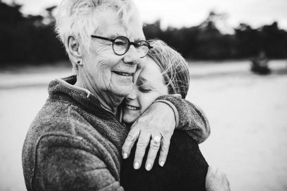 Oma knuffelt met kleindochter in zwartwit op Kootwijkerzand