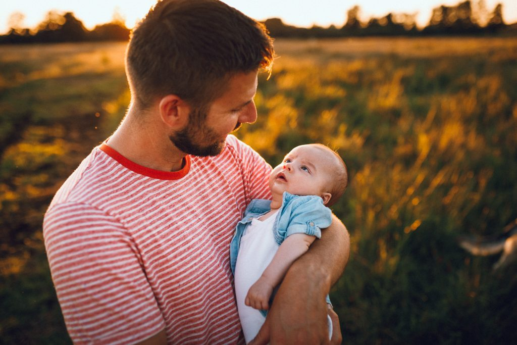 Newbornfoto's buiten papa knuffelt met baby tijdens golden hour vakantieshoot in Hellendoorn