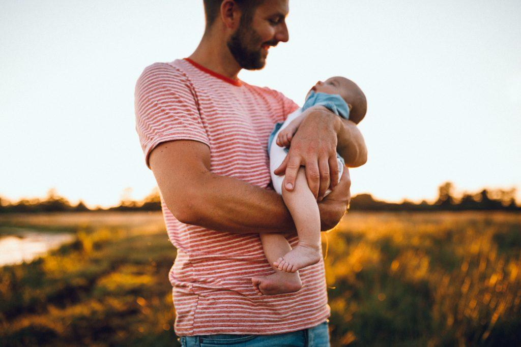 Papa's handen om de benen van de newborn baby tijdens vakantieshoot in Hellendoorn