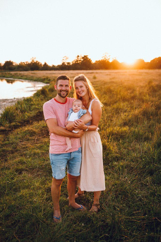 Jong gezin met newborn tijdens familiefotoshoot buiten tijdens golden hour in Hellendoorn op de camping