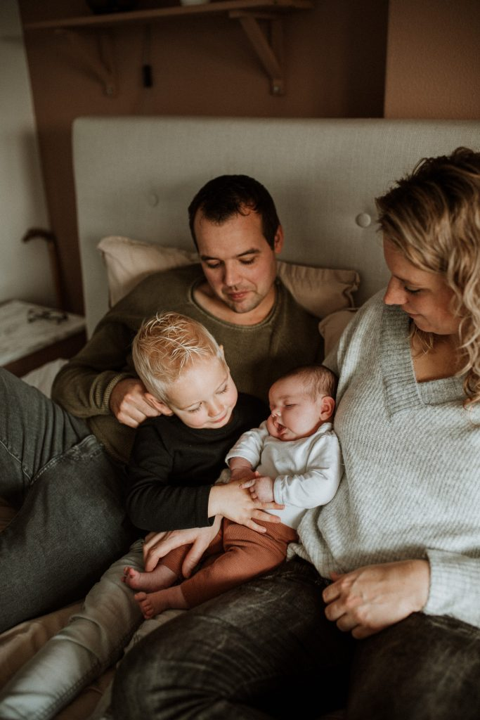 Newborn fotoshoot met hele gezin op bed in Groenlo door Ilse Stronks fotografie, newbornfotograaf Apeldoorn