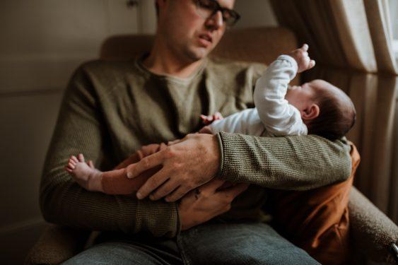 Newborn fotoshoot papa houdt baby in zijn armen in Groenlo door Ilse Stronks fotografie, newbornfotograaf Apeldoorn