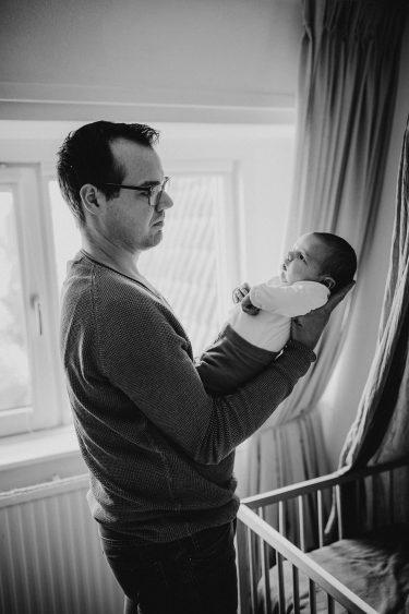 Newborn fotoshoot vader houdt baby in z'n handen in Groenlo door Ilse Stronks fotografie, newbornfotograaf Apeldoorn