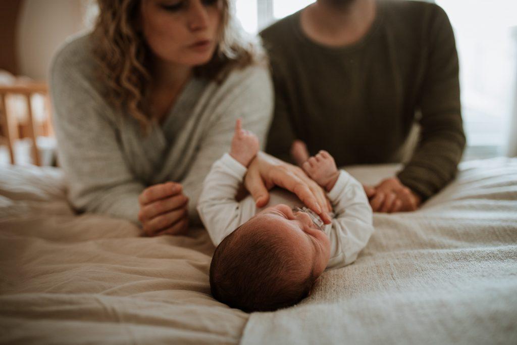 Newborn fotoshoot ouders kijken naar de baby in Groenlo door Ilse Stronks fotografie, newbornfotograaf Apeldoorn