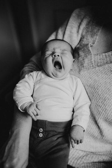 Newbornfotograaf knuffelen met de baby die gaapt in Groenlo door Ilse Stronks fotografie, newbornfotograaf Apeldoorn